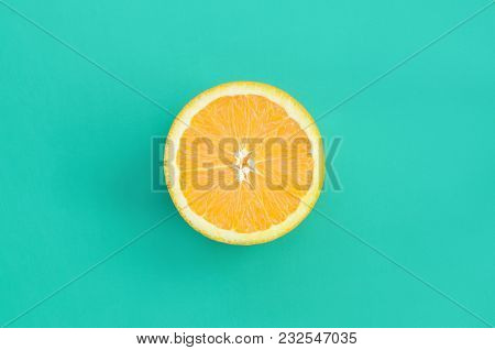 Top View Of A One Orange Fruit Slice On Bright Background In Turquoise Green Color. A Saturated Citr