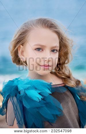 Close-up Portrait Of A Cute Little Girl With A Blond Tress On The Background Of Azure Sea