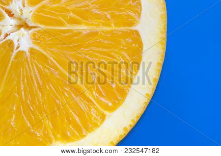 Top View Of A One Orange Fruit Slice On Bright Background In Blue Color. A Saturated Citrus Texture