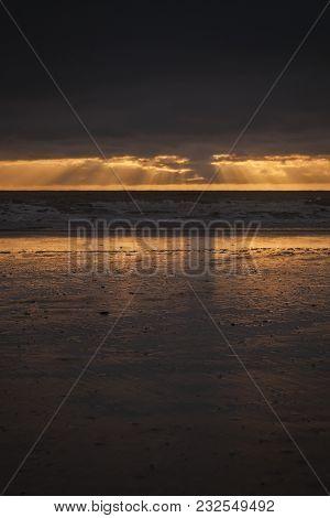 Sunrise At Moeraki Beach, Otago, New Zealand, As The Sun Rises Through Heavy Layers Of Cloud And Cas
