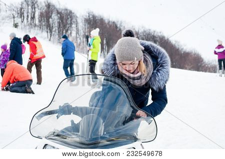 Ukraine, Lviv - 20 Mar, 2018: Beautiful Girl Sits On A Snowmobile On The Background Of People