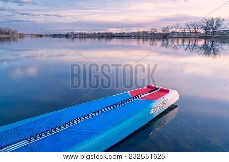 Fort Collins, CO, USA - March 21, 2018: Racing stand up paddleboard on a calm lake at dusk - 2018 model of All Star SUP by Starboard.