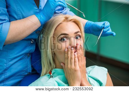 Girl Frightened By Dentist Covers Her Mouth. The Girl Is Afraid Of The Dentist.