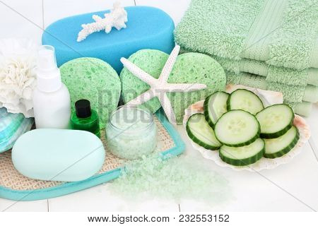 Skin care beauty treatment with cucumber, bath salts, sponges, face cloths, aromatherapy essential oil, body lotion, soap, carnation flower and decorative shells on white wood background.