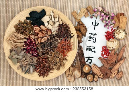 Chinese alternative medicine with herbs on a wooden plate on bamboo background with calligraphy script on rice paper. Translation reads as chinese alternative medicine. Top view.