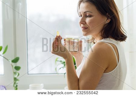 Woman Takes Pill With Omega-3 And Holding A Glass Of Fresh Water With Lemon. Picture Of The House, I