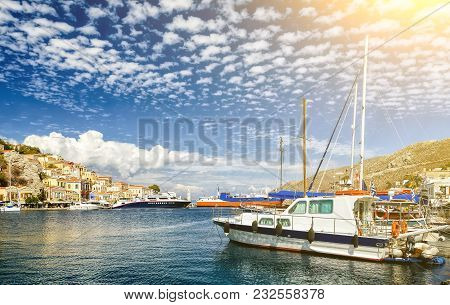 View On Greek Sea Symi Island Harbor Port, Classical Ship Yachts, Houses On Island Hills, Tourists A