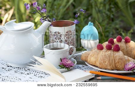 Breakfast With Cup Of Coffee. A Dessert With Croissants And Berries Of Raspberry On White A Lace Tab