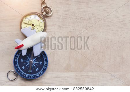 Travel And Vacation Plan Background. Small Airplane Toy With Pocket Watch And Compass On Wood Table.