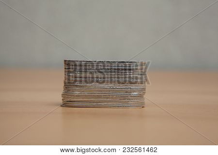 Stack Of Metal Tags On Wooden Floor.