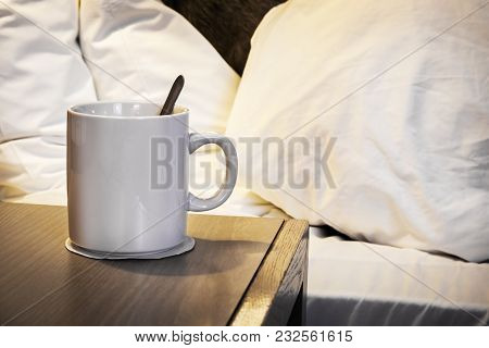 Cup Of Morning Coffee On The Bedside Table In The House Or Hotel Room. In The Background Is A Sleepe