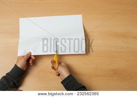 Child Cuts A Paper With A Scissors.
