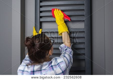 Housemaid Woman Is Cleaning. Wipes The Bathroom Heater With Rag.