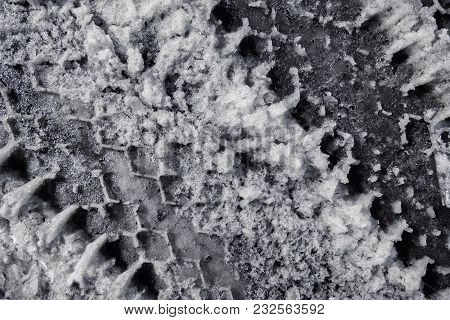 Traces From Car Tires On Snow In The Spring. Spring Time. Dark Grunge Background. Spring Slush