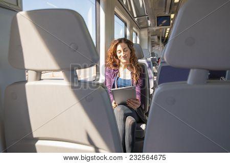 Happy Woman In Train Reading Digital Tablet