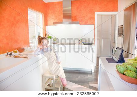 Four Years Old Blonde Child With Apron On Stool O Ladder In The Kitchen Looking At A Digital Tablet