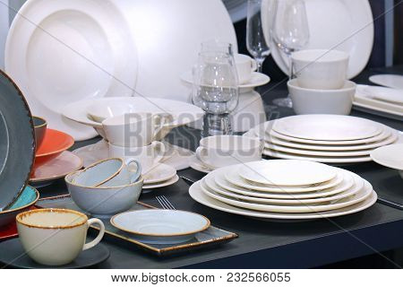White Porcelain Plates Stacked On Table With Ceramic Cups