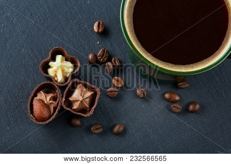 Coffee Cup, Coffee Beans, Chocolate Candies On Stone Board Over Wooden Background, Selective Focus,
