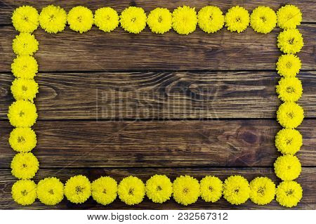 Flower Frame. A Frame Of Yellow Chrysanthemum Flowers On A Brown Wooden Background With A Place For