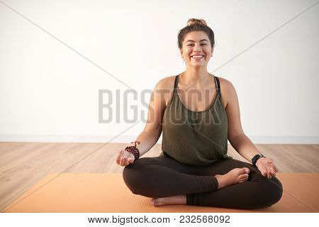 Joyful Obese Woman Wearing Top And Leggings Sitting In Lotus Position And Looking At Camera With Too