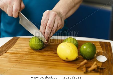 Man Slicing Limes And Lemons On A Wooden Board