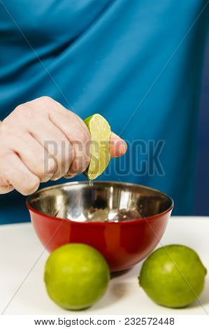Man Squeezing Half A Lime Into A Bowl, Selective Focus