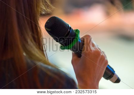 Speaker at conference holding microphone in the hand