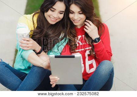 Two Pretty Young Woman With Beautiful Smile Using The Tablet In The Park