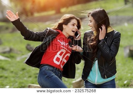 Two Pretty And Happy Young Woman Using The Mobile Phone In The Park. Best Friends