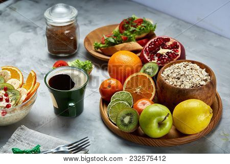Breakfast Still Life With Oatmeal Porridge, Fruits, Coffee Cup Served With Fork, Spoon On Homespun N