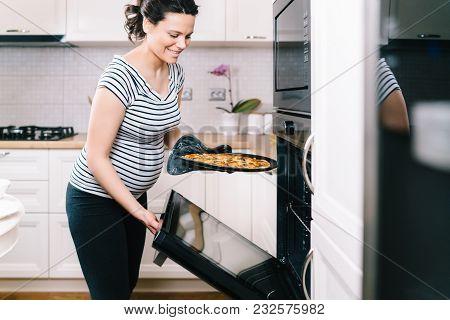 Portrait Of Pregnant Woman Preparing Pizza At Home