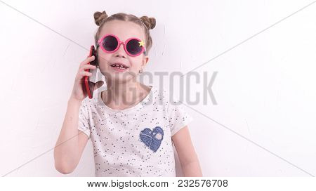Communication Technologies: A Girl In Pink Glasses Emotionally Talks On The Red Phone. Portrait At T