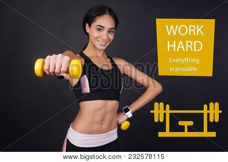 Work Hard. Strong Confident Enthusiastic Sportswoman Feeling Glad While Holing A Yellow Hand Weight
