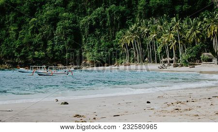 Crystal Bay, Palm Trees On Sandy Beach With Some Local Boats In Ocean. Nusa Penida Bali.