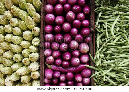 A triptych of vegetables. Bittergourds, aubergines and green beans for sale a Kandy market, Sri Lanka.