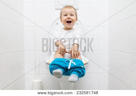 Adorable Young Child Sitting On The Toilet