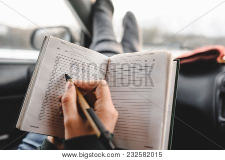 Closeup Shot Of Notebook And Pen In Hands. Inside The Car. Ready To Write. Making A Plan Of Trip