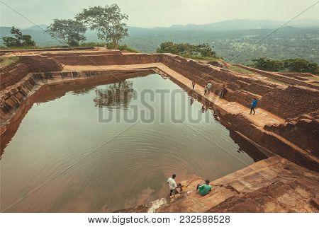 Sigiriya, Sri Lanka - Jan 9, 2018: People Relaxing Around Ancient Pond Of Sigiriya City With Ruins A