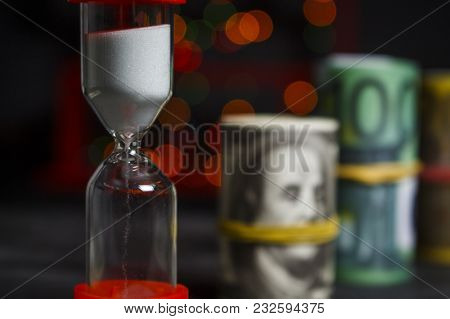 Hourglass With A Bunch Of Dollars And Euros