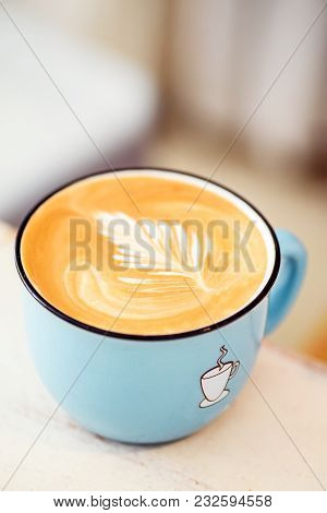 A Cappuccino Mug With A Pattern On The Foam. Morning Drink In A Beautiful Blue Cup On A Light Backgr