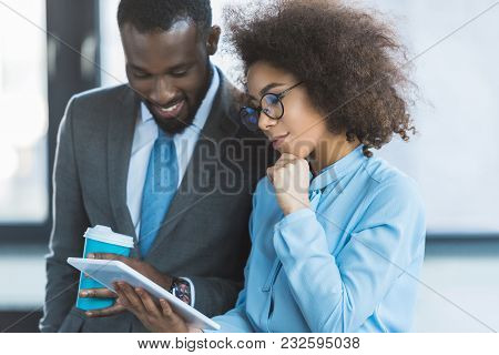 Smiling African American Businesspeople Looking At Tablet In Office