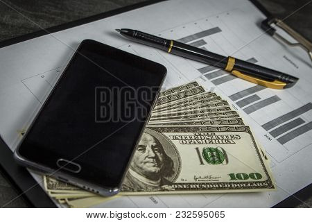 Black Ballpoint Pen With A Bunch Of Dollars And A Mobile Phone