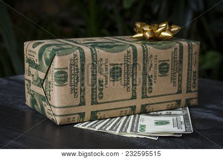 Gift In A Box With A Picture Of Dollars And A Golden Bow On A Dark Table