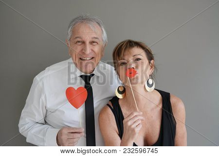 Cheerful senior couple with photobooth props, isolated