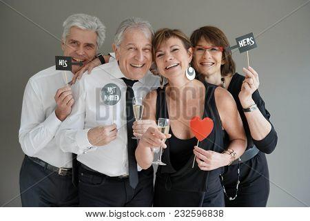 Senior couples celebrating wedding and using photo props