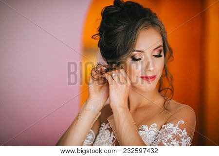 Beautiful Young Bride With Wedding Makeup And Hairstyle In Bedroom Bride Holds A Beautiful Wedding D