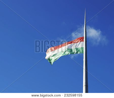 The National Flag Of Hungary Against Blue Sky