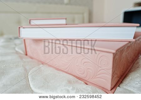 Gentle Pink Wedding Photobook Or Photo Album, Box, And Cd Case Laying On The Bed.