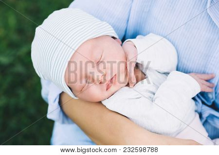 Loving Mother With Her Newborn Baby On Her Arms.