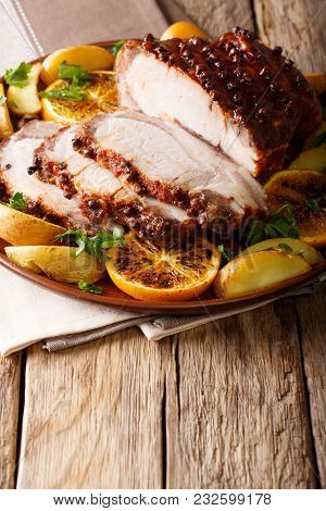 Glazed Roast Pork With Potatoes, Oranges And Apples Close-up. Vertical